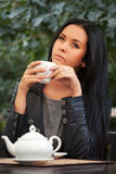 Young woman drinking tea at sidewalk cafe Stock Photo