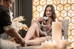 Young woman drinking tea during traditional Balinese foot massage stock image