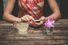 Young woman drinking tea and using her phone. A young woman is drinking tea and using her smart phone at a wooden table Royalty Free Stock Photo