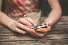 Young woman drinking tea and using her phone Stock Photos