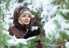 Young woman is drinking tea in the winter forest. Stock Photography