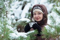 Young woman is drinking tea in the winter forest. Royalty Free Stock Photo