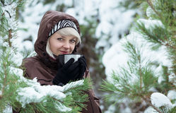 Young woman is drinking tea in the winter forest. Stock Photos