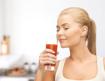 Young woman drinking tomato juice Stock Images