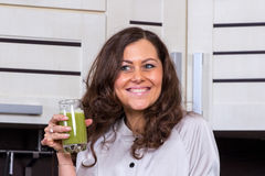 Young woman with drinking vegetable juice. In kitchen Royalty Free Stock Images