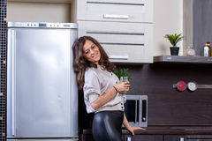 Young woman with drinking vegetable juice. In kitchen Royalty Free Stock Image