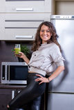 Young woman with drinking vegetable juice. In kitchen Stock Photography