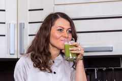 Young woman with drinking vegetable juice. In kitchen Royalty Free Stock Photography
