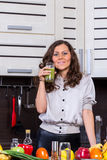 Young woman with drinking vegetable juice. In kitchen Stock Photo