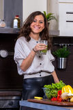 Young woman with drinking vegetable juice. In kitchen Stock Image