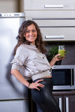 Young woman with drinking vegetable juice. In kitchen Royalty Free Stock Photo