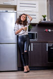 Young woman with drinking vegetable juice. In kitchen Stock Images