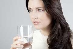 Young woman drinking water. Portrait of a young woman drinking a glass of water Royalty Free Stock Images