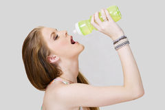 Young woman drinking water. From plastic sports bottle Royalty Free Stock Image