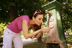 Young woman drinking water. A young woman drinking from a water fountain Royalty Free Stock Image
