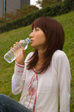 Young woman drinking water. Young Asian woman drinking mineral water Royalty Free Stock Photo