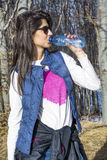 Young Woman Drinking Water in the autumn forest Royalty Free Stock Photo