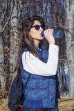 Young Woman Drinking Water in the autumn forest Royalty Free Stock Images