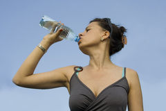 Young woman drinking water from a bottle. Isolated on blue Stock Images