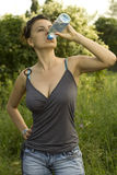 Young woman drinking water from a bottle. In a park Stock Photography