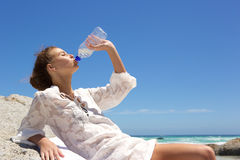 Young woman drinking water from bottle at the beach Stock Images