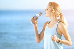 Young woman drinking water from bottle after fitness exercises on beach