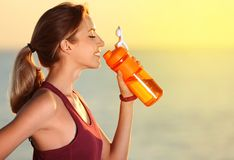Young woman drinking water from bottle after fitness exercises