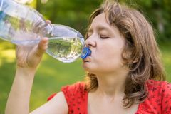 Young woman is drinking water from bottle at sunny hot day royalty free stock photos