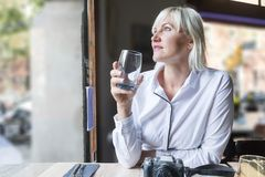 Young woman drinking water in a cafe stock photo