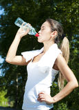 Young woman drinking water after exercise. Summer park background Stock Photography