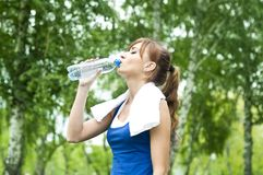 Young woman drinking water after exercise Stock Photos