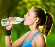Young woman drinking water after fitness exercise Royalty Free Stock Photos