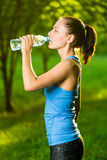 Young woman drinking water after fitness exercise Stock Photos