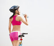 Young woman drinking water and folding bike Royalty Free Stock Image