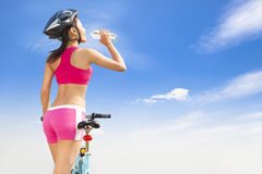 Young woman drinking water with folding bike Stock Image