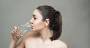 Young woman drinking water from the glass Stock Photos
