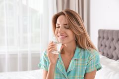 Young woman drinking water from glass. In bedroom royalty free stock photo