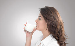 Young woman drinking water. On gray background with clipping path Royalty Free Stock Photo