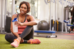 Young woman drinking water in a gym, with copy space. Young women drinking water in a gym, with copy space royalty free stock photos