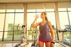 Young woman drinking water in gym Stock Photo