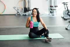 Young woman drinking water in gym, Royalty Free Stock Photos