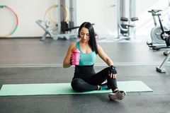 Young woman drinking water in gym, Stock Image