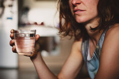 Young woman drinking water at home Stock Image
