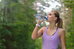Young woman drinking water after jogging Royalty Free Stock Photo