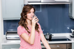 Young woman drinking water in kitchen Royalty Free Stock Images