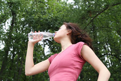 Young woman drinking water. Young woman drinking water during morning jogging in the park Stock Images