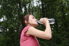 Young woman drinking water. Young woman drinking water during morning jogging in the park Royalty Free Stock Photo