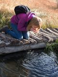 Young woman drinking water from outdoor stream with her hands. Royalty Free Stock Photography