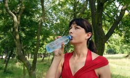 Young woman drinking water outdoors Stock Photography