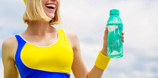 Young woman drinking water after run. Woman in sports wear is holding a bottle of water. Sports girl drinks water from a